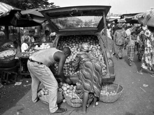 Une africaine achetant des fruits au marché de Cotonou.