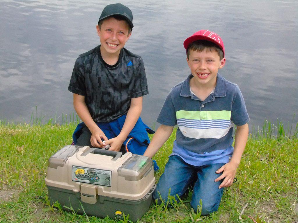 Deux jeunes garçons et leur coffre à pêche